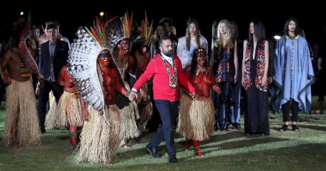Founder of Cavalera, Hiar, walks with indians of Yawanawa ethnicity after presenting creations from the Cavalera Summer 2016 Ready To Wear collection during Sao Paulo Fashion Week in Sao Paulo