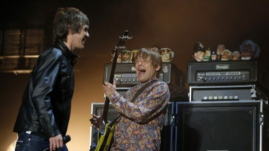 Ian Brown (L) of British band The Stone Roses laughs with bassist Mani (R) as he performs on stage on the opening night of their 3 night series of reunion concerts at Heaton Park in Manchester, northern England, June 29, 2012. REUTERS/Phil Noble (BRITAIN - Tags: ENTERTAINMENT SOCIETY)