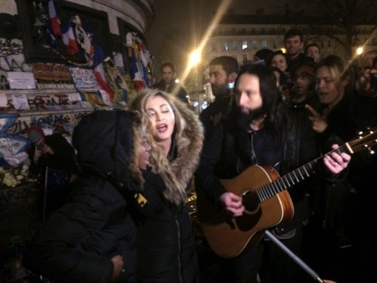 US singer Madonna (C) sings next to her guitarist Monte Pittman (C-R) and her adoptive son David Banda (L) on December 10, 2015 at the place de la Republique in Paris at a makeshift memorial in tribute to victims of November 13 terror attacks in Paris.