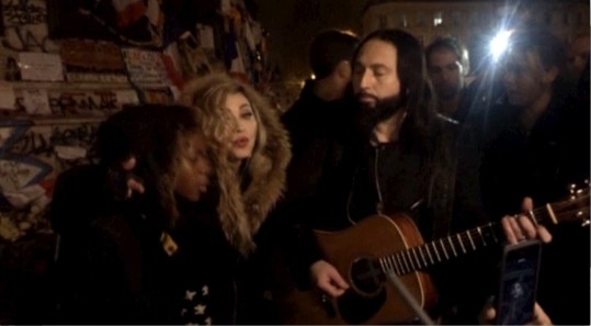 A still image from a video shows singer Madonna (C) giving an impromptu street concert at the Place de la Republique in Paris December 10, 2015, the site of massed tributes for the victims of the recent Paris attacks. Madonna performed John Lennon's 'Imagine' and her song 'Ghosttown', accompanied just by a guitar in the middle of the cold night. REUTERS TV