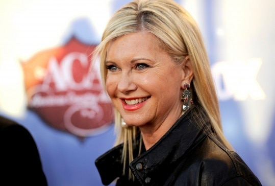 FILE - In this Tuesday, Dec. 10, 2013, file photo, Olivia Newton-John arrives at the American Country Awards at the Mandalay Bay Resort & Casino, in Las Vegas. The 65-year-old singer and actress announced a headlining residency Tuesday, Feb. 4, 2014. She will perform 45 shows at the Donny and Marie Showroom at The Flamingo, starting April 8. Dates are scheduled through the summer. (Photo by Chris Pizzello/Invision/AP, File)