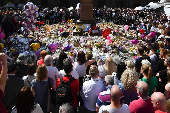 TOPSHOT - People stop to observe a minute's silence in St Ann's Square gathered around the tributes, in central Manchester, northwest England, on May 25, 2017, as a mark of respect to the victims of the May 22 terror attack at the Manchester Arena. Police said they arrested two men Thursday in the Manchester area in connection with the deadly bombing of an Ariana Grande pop concert, while a detained woman was released without charges. Britain has raised its terror alert to the maximum level and ordered troops to protect strategic sites after 22 people were killed in a suicide bomb attack on a Manchester pop concert. / AFP PHOTO / Ben STANSALL